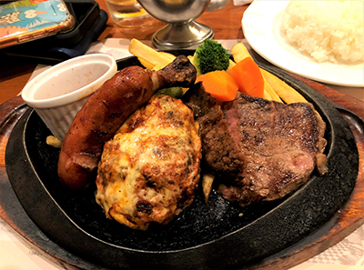 An example of a Westernized Japanese food (Yoshoku). On this platter, it includes Hambagu (hamburger steak), sausage, rice and vegetables.